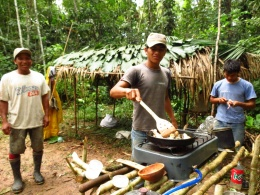 Frying up the frog in our hunting camp. The Boras quickly constructed the shelter with their machetes and it came in good use when the rain hit