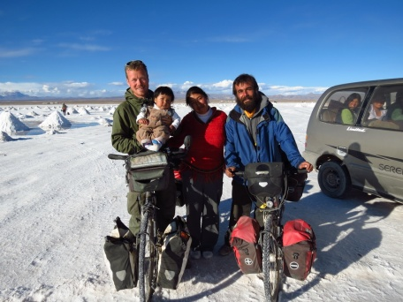 While cycling across the impressive Salar de Uyuni in Bolovia, a local family rushes out of her car to meet the foreigners and have a photo taken, instantly handing her baby to Henrik