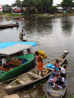 Bananas off, schoolgirls rowing their own boat. A very lively little port in Leticia