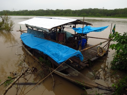 """Our raft and our boat. Due to the massive amount of mosquitoes, we had sown a huge box of a mosquito net that we all could sit inside. In the photo, it is the blue thing that is """"rolled up"""" in the front of the raft"""