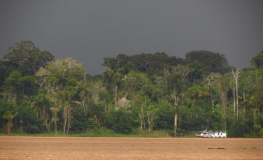 A little Brazilian cargo vessel is transiting near the shore as dark clouds are promising rain
